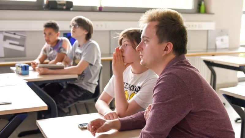 Jongeren zitten met leerkracht op de schoolbanken